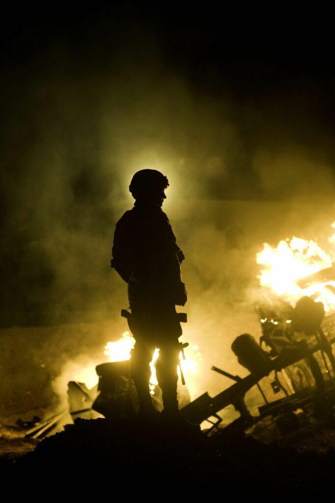 Ein Soldat steht zwischen den Trümmern eines zerstörten Hauses, seine Silhouette zeichnet sich in grellem Licht ab
