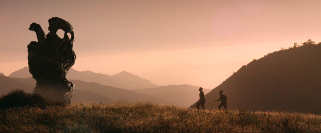 Aaron und Justin laufen vor einem rötlich leuchtenden Himmel, links steht eine mysteriöse Steinformation