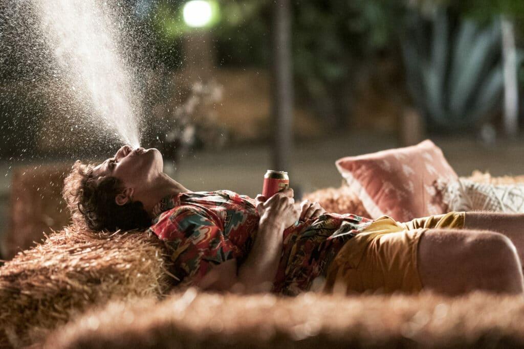 Einer der Hauptdarsteller aus Palm Springs liegt auf dem Sofa und spuckt sein Getränk in hohem Bogen aus