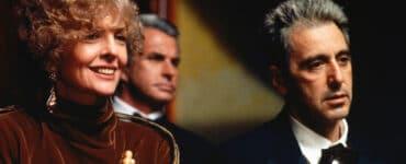 Diane Keaton trägt in Der Pate Epilog ein rotes Samtkleid mit einer goldenen Traubenbrosche, außerdem hat sie kurze gelockte Haare und sie lächelt. Al Pacino steht direkt neben ihr mit schwarzem Anzug und Fliege und schaut ausdruckslos in dieselbe Richtung.