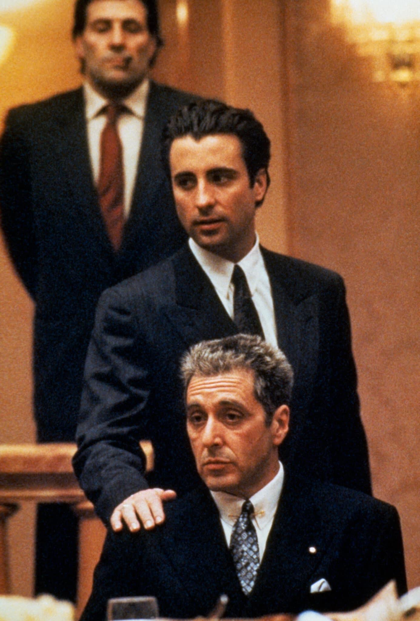 Andy Garcia und Al Pacino tragen in Der Pate Epilog: Der Tod von Michael Corleone beide dunkle Anzüge und sind in einem holzgetäfelten hellen Raum. Al Pacino sitzt an einem Tisch, Andy Garcia steht direkt hinter ihm und legt ihm die Hand auf die Schulter.