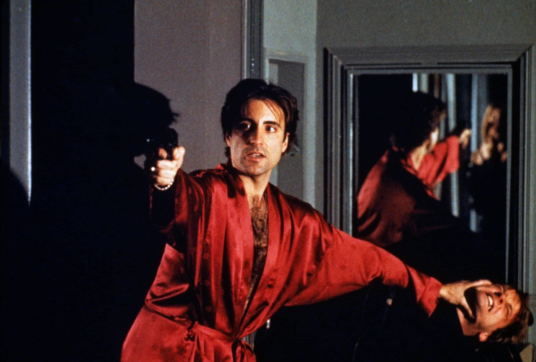 Andy Garcia trägt in Der Pate Epilog einen roten Morgenmantel. Er drückt einen Angreifer zu Boden und richtet seine Waffe auf eine zweite Person.