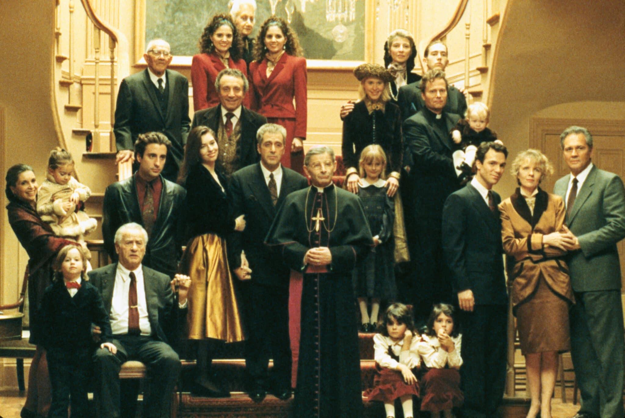 Der gesamte Cast von Der Pate Epilog: Der Tod von Michael Corleone steht auf einer Treppe und posiert für ein Foto.
