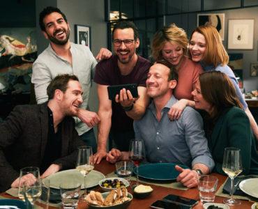 Die Besetzung von Das perfekte Geheimnis sitzt am Essenstisch und schaut lachend auf das Smartphone von Pepe (Florian David Fitz)