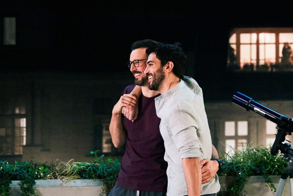 """Pepe (Florian David Fitz) und Leo (Elyas M'Barek) liegen sich auf dem Balkon in """"Das perfekte geheimnis) lachend in den Armen"""