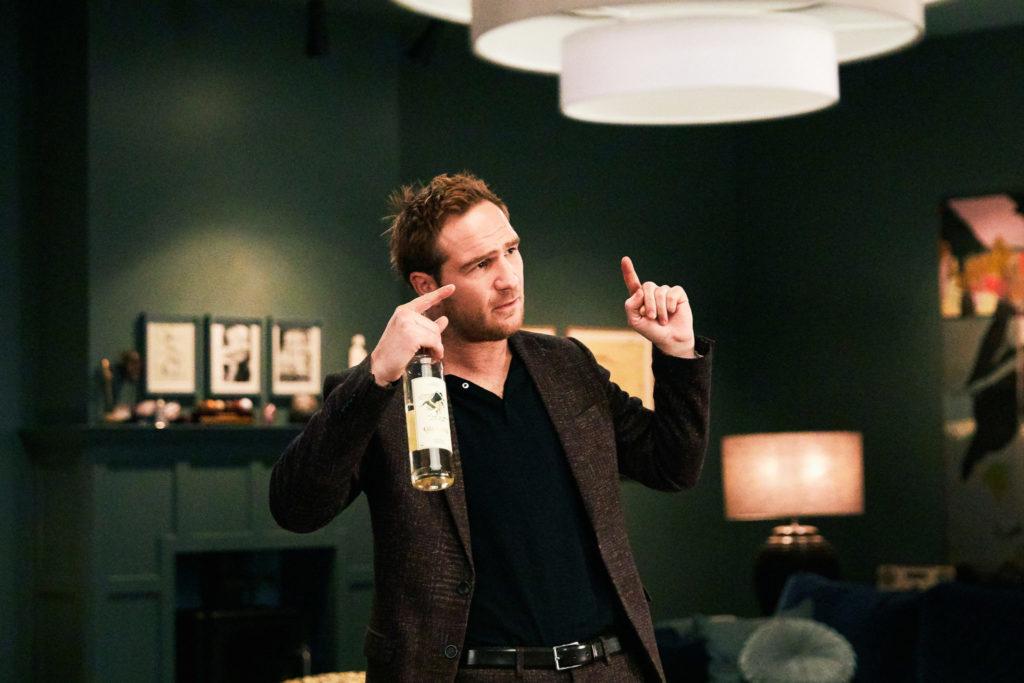 Simon (Frederick Lau) diskutiert, während er eine Weinflasche in der Hand hält