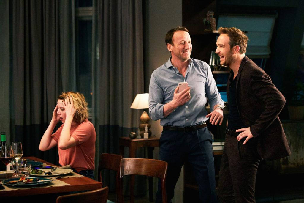 Simon und Rocco lachen stehend, während Bianca schockiert am Tisch sitzt