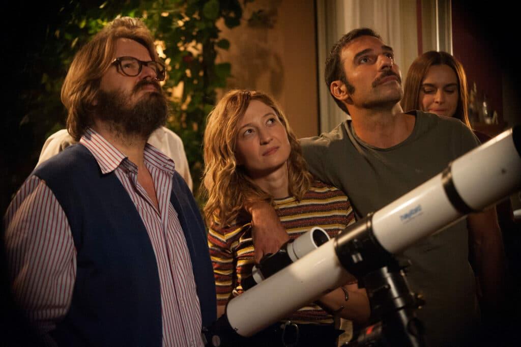 Peppe, Bianca, Cosimo und Eva stehen vor einem Teleskop auf dem Balkon und schauen in den Himmel