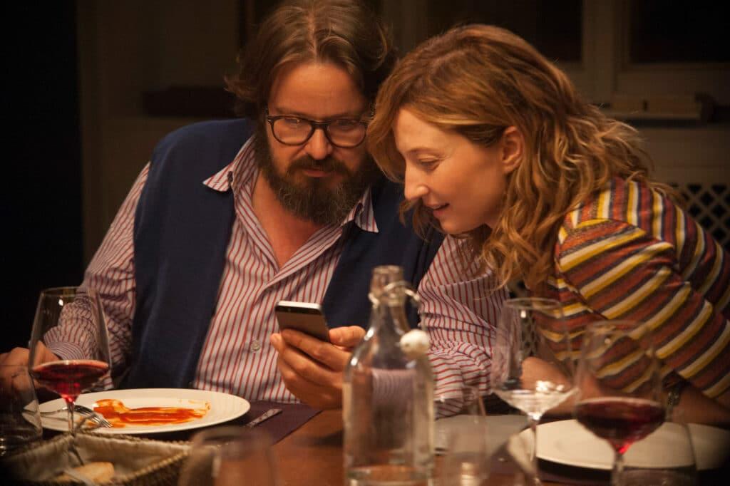 Peppe und Biance sitzen nebeneinander am Wohnzimmertisch und schauen auf Peppes Handy in Perfetti Sconosciuti