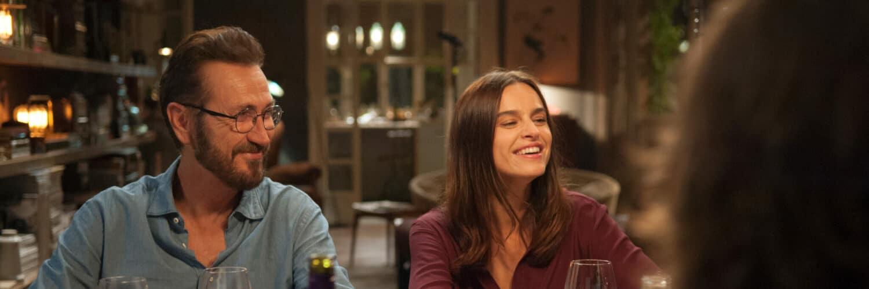 Rocco und Eva sitzen grinsend nebeneinander am reich gedeckten Wohnzimmertisch in Perfetti Sconosciuti