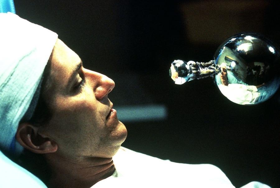 Hauptfigur Mike (Michael Baldwin) liegt mit Kopfverband im Krankenbett, vor ihm eine schwebende Silberkugel