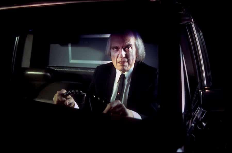 Der Tall Man (Angus Scrimm) sitzt am Steuer eines Leichenwagens und blickt mit gehobener Augenbraue in die Kamera