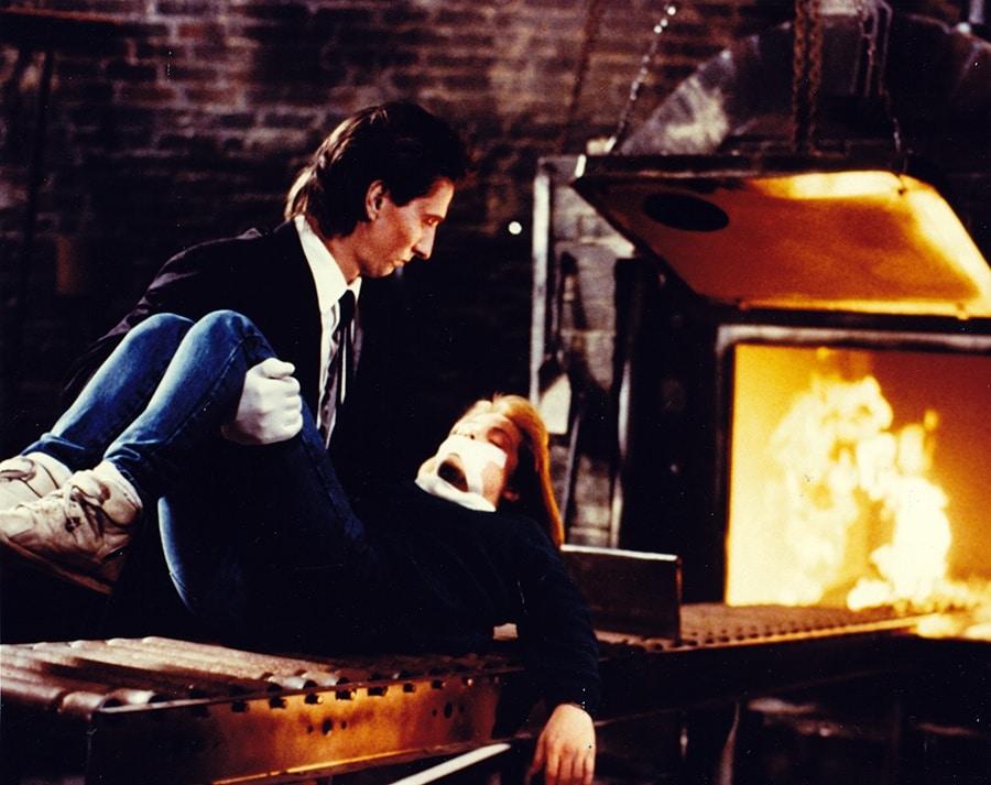 Ein schwarz gekleideter Gehilfe des Tall Man legt die geknebelte Liz auf das Förderband eines Verbrennungsofens