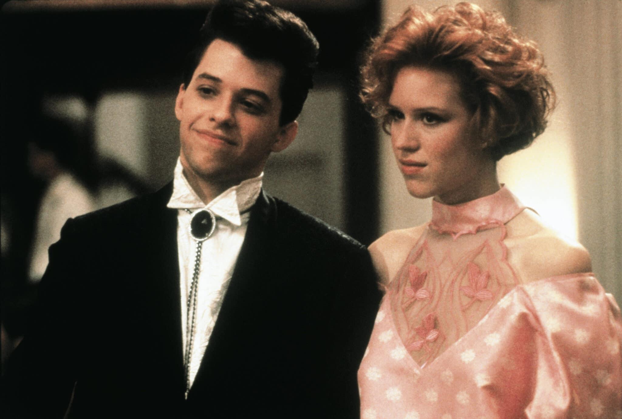 """Jon Cryer steht als Duckie im schicken Anzug händchenhaltend neben Molly Ringwald als Andie, die ein pinkes Ballkleid trägt, in """"Pretty In Pink""""."""