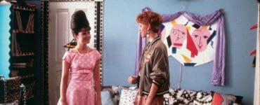 Andie steht mit einer Frau in rosa in einem schrillen Zimmer
