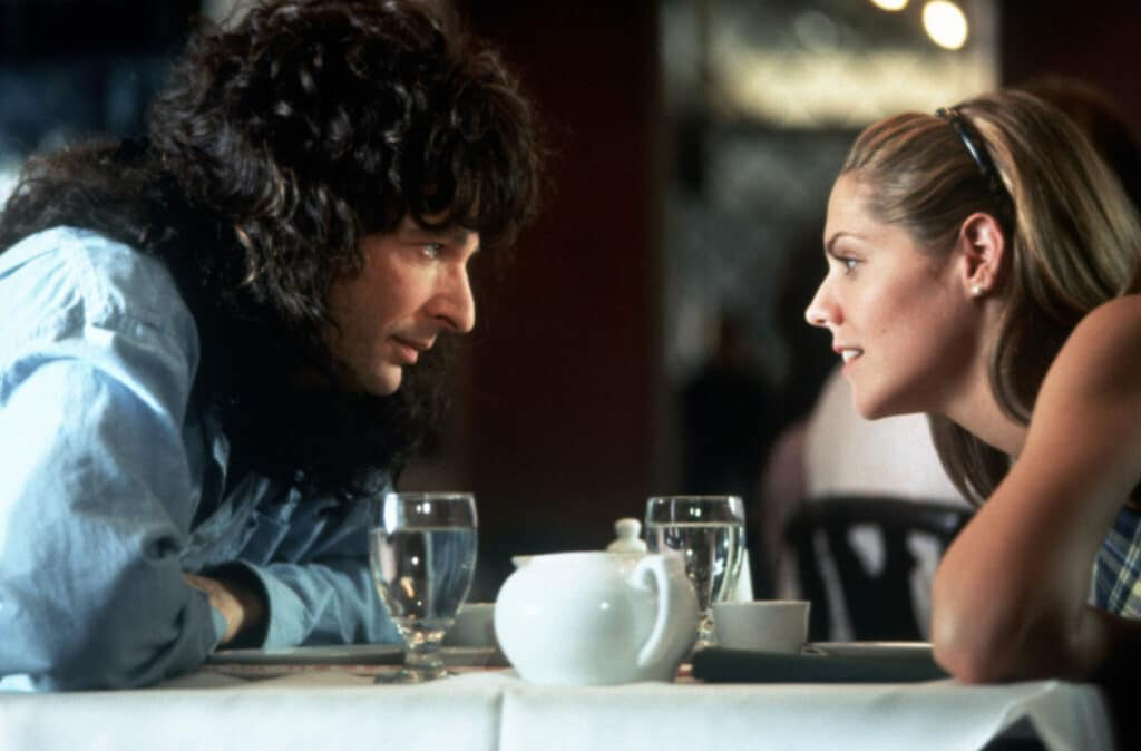 Howard sitzt auf der linken Seite eines Tisches seiner Freundin zugeneigt. Sie lehnen sich über den Tisch herüber und blicken einander an.