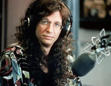 Howard Stern ist in einer Nahaufnahme zu sehen und blickt in die Kamera. Er trägt Kopfhörer und rechts neben ihm ist sein Mikrofon für die Aufnahme seiner Radioshow zu erkennen.