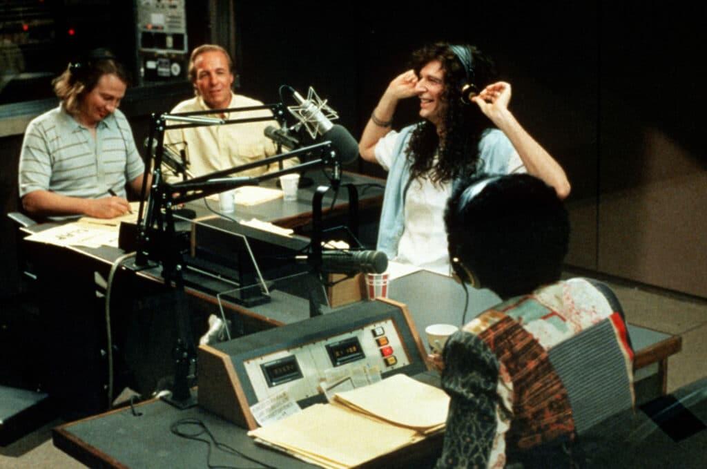 Howard Stern sitzt zusammen mit zwei Co-Moderatoren und einem Gast im Studio. Howard sitzt rechts außen am Tisch, zwischen ihm und dem Co-Moderator auf der linken Seite hat der Gast Platz genommen. Unterhalb von Howard sitzt seine Co-Moderatorin.