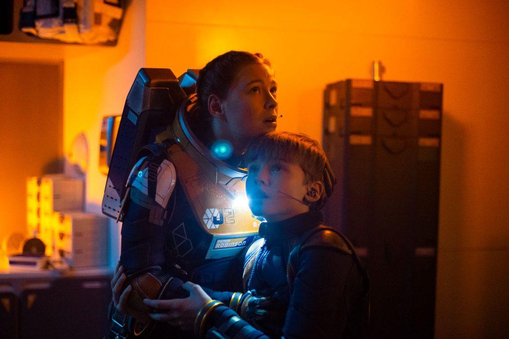 Eine Frau und ein Kind umarmen sich in Weltraumanzügen, oranges und blaues Licht