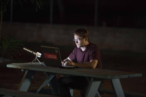 Edward sitzt an einem Laptop und einer Antenne in einem Garten