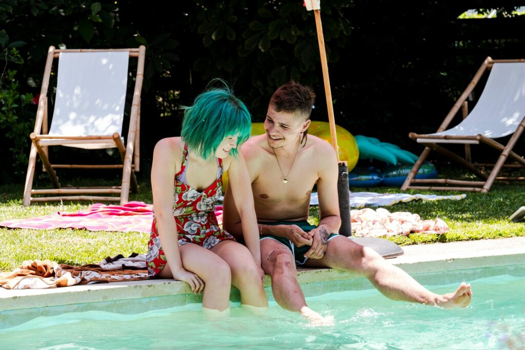 Milla und Moses sitzen gemeinsam am Pool und lachen