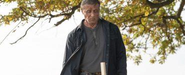 Sylvester Stallone steht als Rambo vor einem Grab.