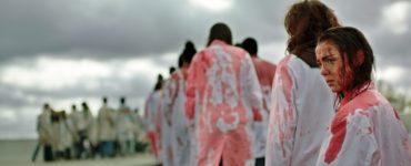 Viele Menschen in weißen blutverschmierten Kleider sind von hinten zu sehen