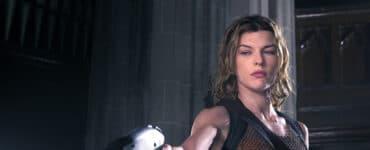 Alice, gespielt von Milla Jovovich, steht in einem braunen Top und mit mehreren Waffen ausgestattet und richtet ihre Pistole auf einen Gegner am Boden