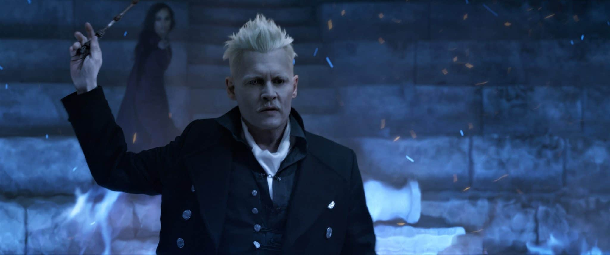 Gellert Grindelwald (Johnny Depp) erhebt bedrohlich seinen Zauberstab in der rechten Hand. Im Hintergrund zielt eine Hexe mit ihrem Stab in seine Richtung.