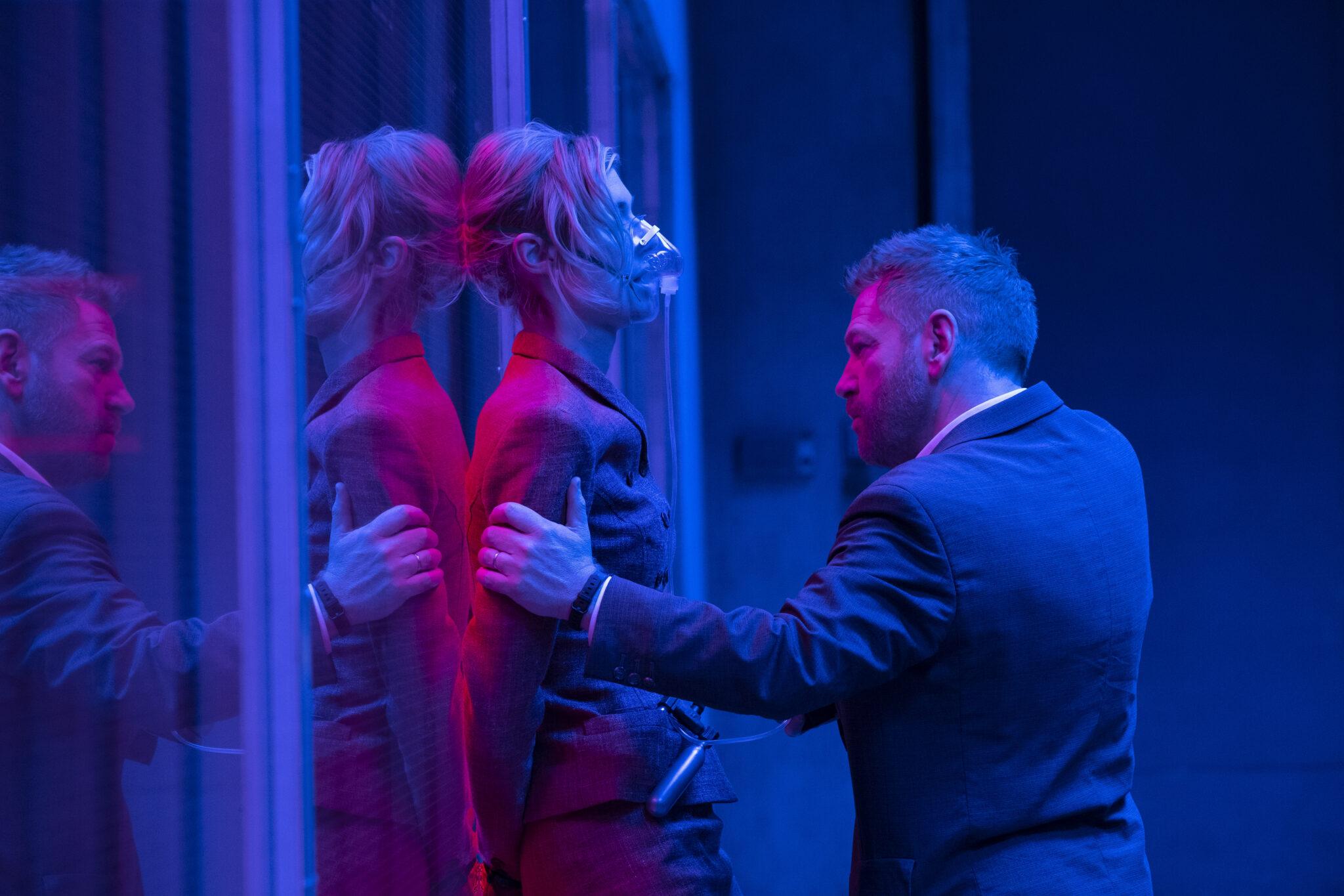 Eine Frau wird von einem Mann gegen eine Glasscheibe gedrückt