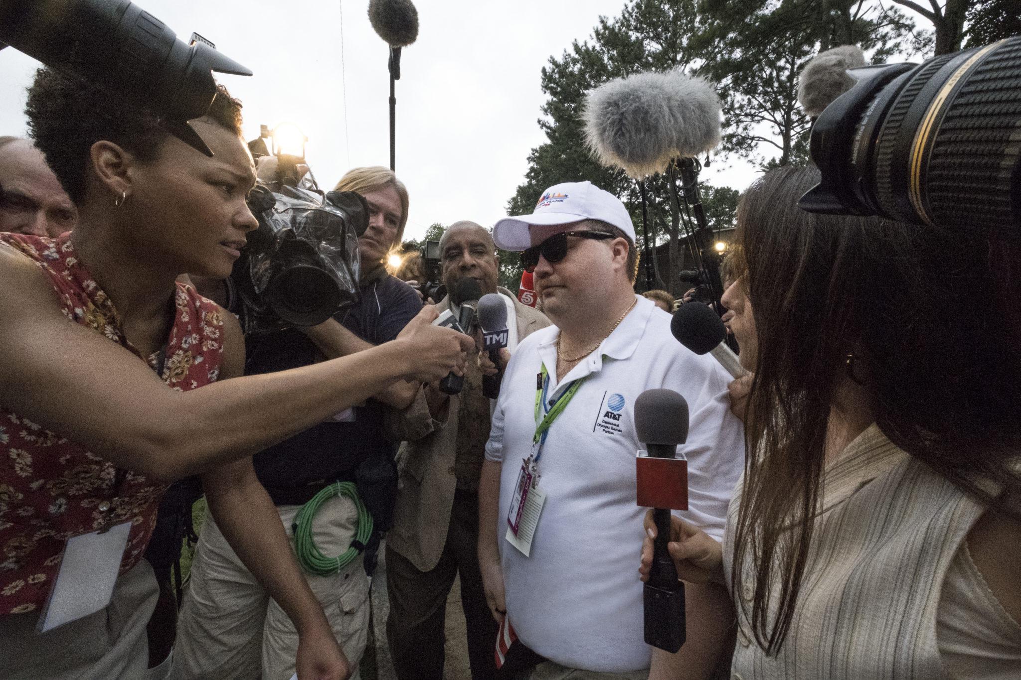 Richard Jewell ist umringt von Reportern, die alle versuchen einen O-Ton von ihm zu bekommen. Dabei trägt der Mann seine normale Arbeitskleidung