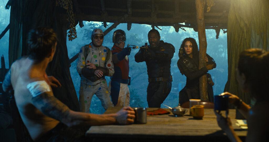 Polka-Dot Man, Peacemaker, Bloodsport und Ratcatcher II dringen mit gezogenen Waffen in eine Hütte ein, wo Rick Flag mit der Rebellenführerin am Tisch sitzt und Tee trinkt - The Suicide Squad.