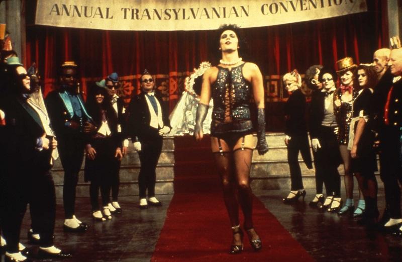 Der in Strapse gekleidete und geschminkte Wissenschaftler Frank'n'Furter stolziert vor seinen Anhängern - Die besten 10 Filme der 70er