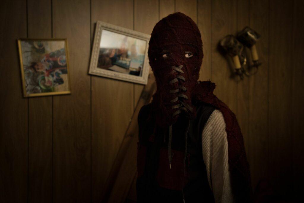 Brandon steht in seinem Kostüm vor einer Wand mit Bildern und sieht Richtung Kamera