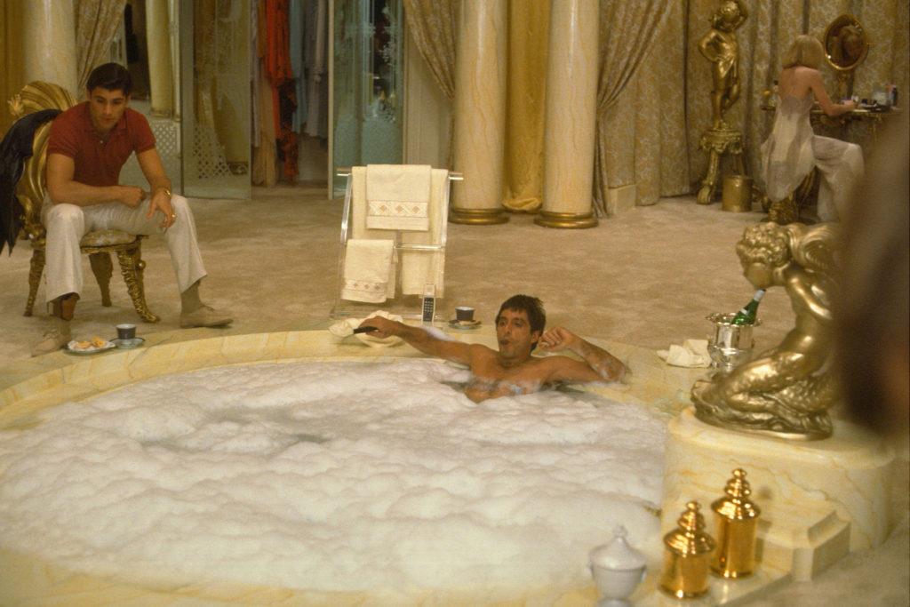 Tony Montana, gespielt von Al Pacino, liegt in einer protzigen Riesenbadewanne und hört Manolo, gespielt von Steven Bauer zu. Im Hintergrund sitzt Elvira, gespielt von Michelle Pfeiffer, an einer Frisierkomode