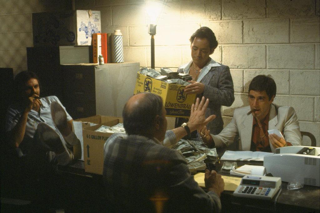 Tony Montana, gespielt von Al Pacino, beim Zählen der Einnahmen. Das Geld, das er selbst waschen will, wird in Kartons angeliefert. Um ihn herum sitzen mehrere Gehilfen.