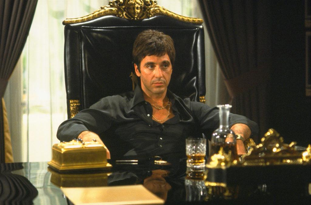Tony Montana, gespielt von Al Pacino, sitz auf seinem thronartigen, goldbeschlagenen Lederseesel hinter seinem überladenen Schreibtisch.