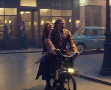 Victor (Daniel Auteuil) und Margot (Doria Tillier) fahren lachend mit einem Moped über die Straße, im Hintergrund ist die Kulisse des Cafés zu sehen.