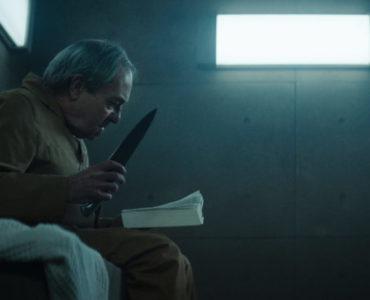 Ein Mann sitzt mit einem Besser auf dem Bett in Der Schacht