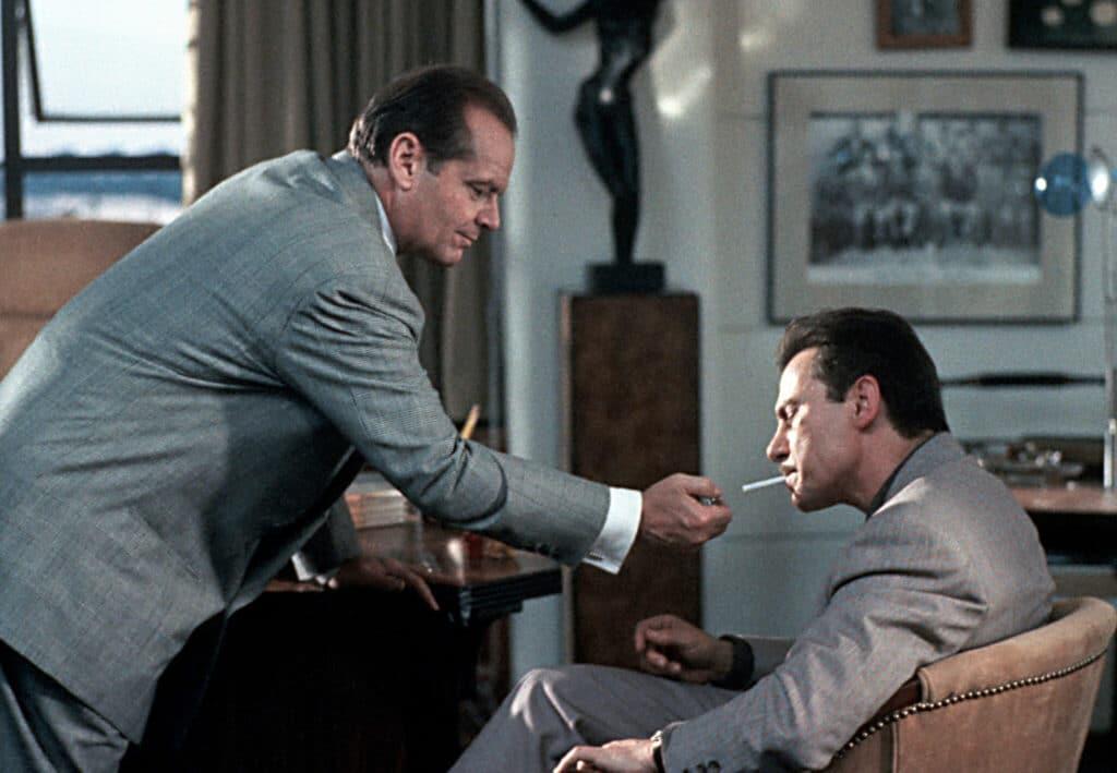 Gittes ist auf der linken Seite des Bildes zu erkennen. Er beugt sich zu seinem auf der rechten Bildseite sitzenden Klienten vor und reicht ihm Feuer. Beide tragen graue Anzüge.