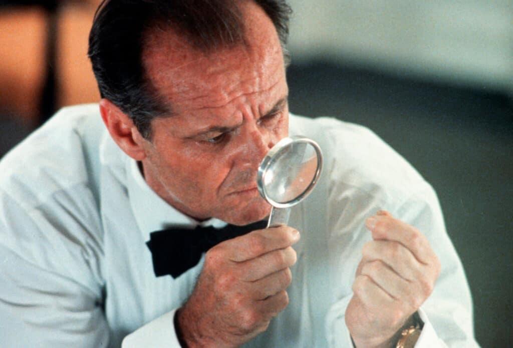 Privatdetektiv Gittes (Jack Nicholson) ist in einer Nahaufnahme zu erkennen. Konzentriert blickt er durch eine Lupe auf etwas Winziges zwischen seinen Fingern.