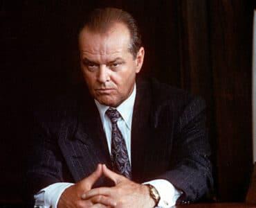 Gittes (Jack Nicholson) lunzt grimmig in Nahaufnahme und faltet seine Hände ineinander. Er trägt einen dunkelgrauen Anzug mit weißen Streifen, ein weißes Hemd und eine Krawatte.