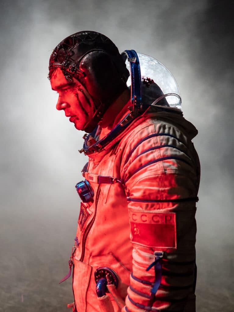 In Sputnik steht Astronaut Konstantin im roten Licht vor einer Rauchwolke