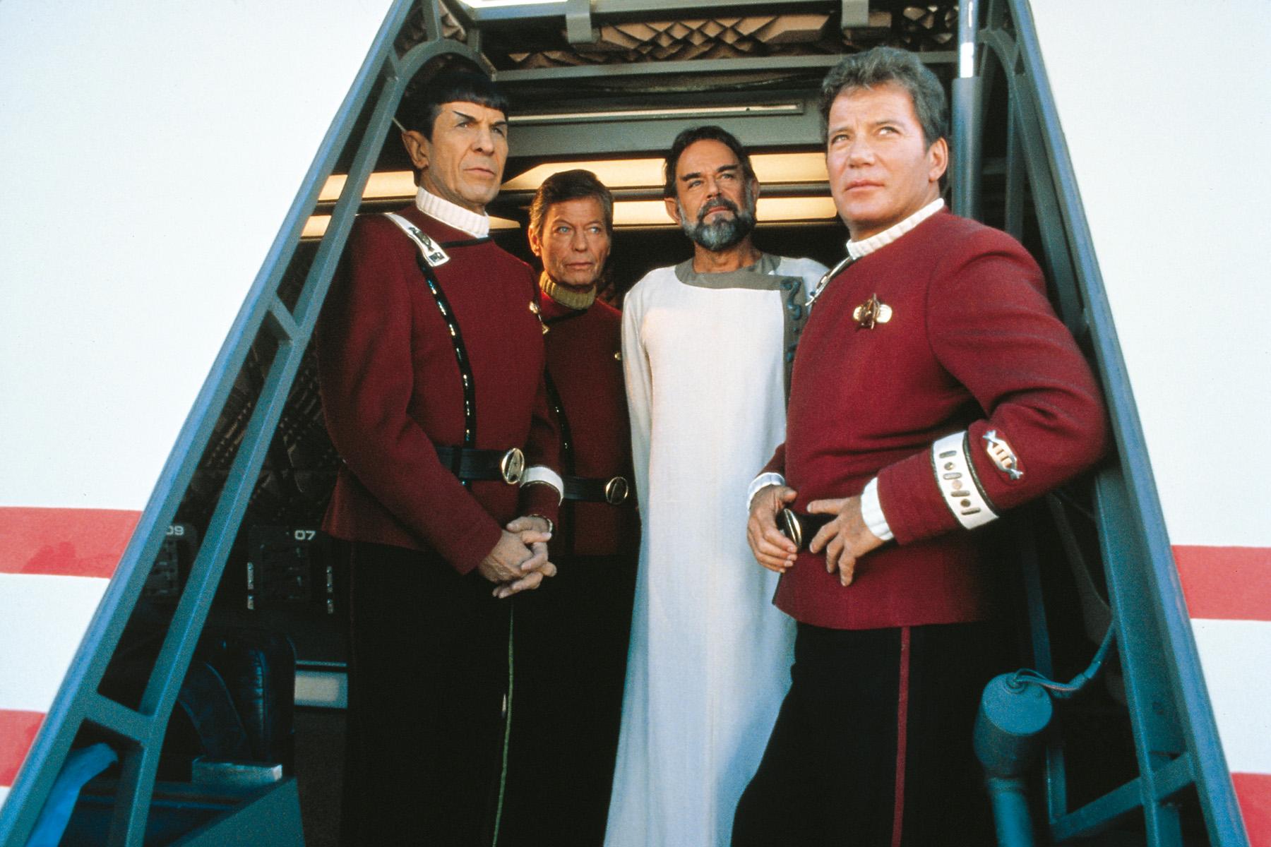 """Leonard Nimoy als Mr. Spock, DeForest Kelley als """"Pille"""" McCoy, Laurence Luckinbill als Sybok und William Shatner als James T. Kirk stehen in einem offenen Raumschiffportal und blicken in den Himmel in """"Star Trek V - Am Rande des Universums""""."""