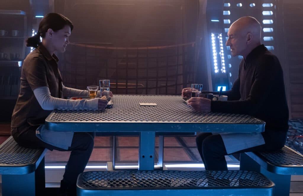 Picard sitzt Soji, gespielt von Isa Briones, an einem Tisch gegenüber.