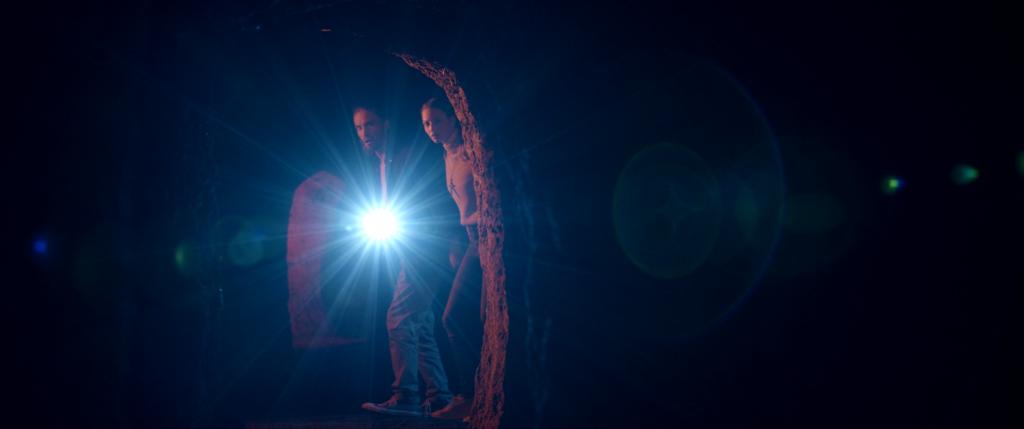 Alina (Tabea Georgiamo) und Thomas (Michael von der Brelie) leuchten mit der Taschenlampe durch einen dunklen Gang in den Katakomben des unheimlichen Klosters.