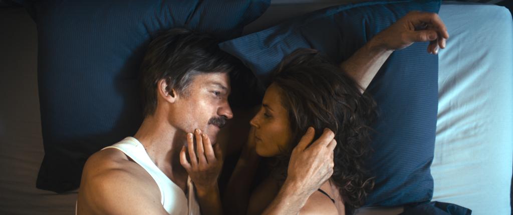 Max (Nikolaj Coster-Waldau) liegt mir seiner Frau Lærke (Tuva Novotny) im Bett, sie schauen sich gegenseitig in die Augen und streicheln sich zärtlich über die Wange und das Haar.