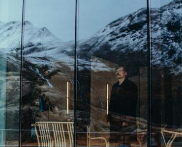 Max (Nikolaj Coster-Waldau) steht im Hotel vor einer Fensterwand und schaut hinaus auf die schneebedeckten Berge.