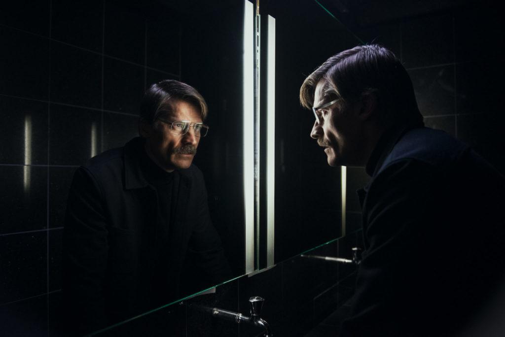 Max (Nikolaj Coster-Waldau) steht in einem dunklen Raum mit schwarzen Fließen vor einem Spiegel und sieht sich selbst in die Augen.