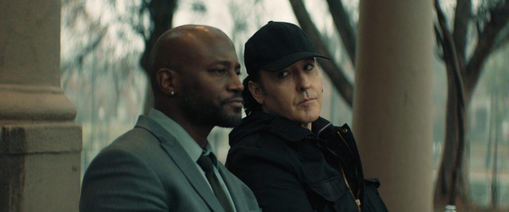Taye Diggs als Richter Coleman sitzt neben John Cusack als Detective Horace auf einer Bank.